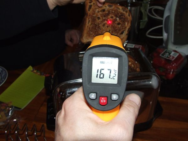 Thermometer pointing at a slice of raisin toast that has just popped out of a toaster