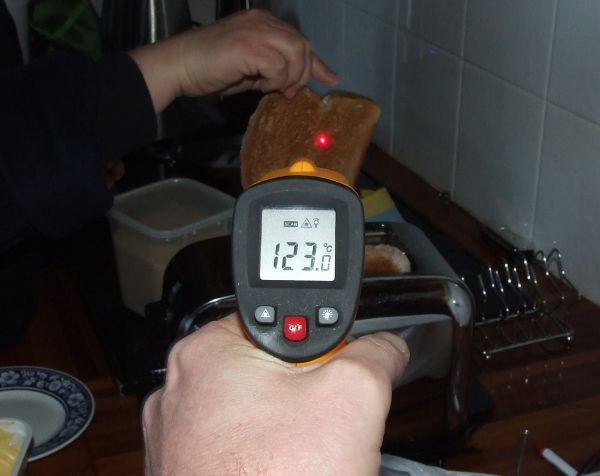Thermometer pointing at a slice of taost that has just popped out of a toaster